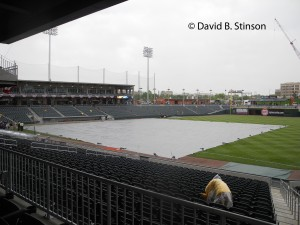 A Lone Stadium Usher Tries In Vain To keep The Rain Away at BB&T Ballpark in Charlotte, North Carolina